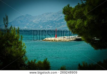 Beautiful View Of Small Lighthouse On Stone Pier Through Green Coniferous Trees In Front Of Biokovo