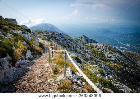 Mountain Path On The Top Of Peak Sveti Jure In Front Of Hills And Rocks Of Biokovo Mountain Range Wi