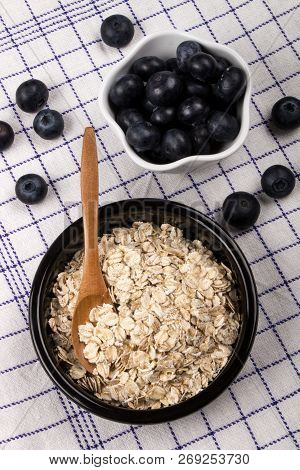 Traditional Irish Oatmeal In A Black Bowl With Wooden Spoon And Healthy Blueberries