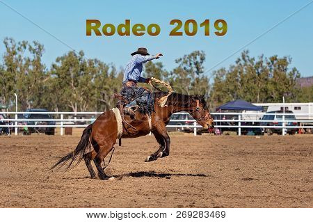 Rodeo 2019 Caption Text.  Cowboy Riding A Bucking Bronco Horse In A Competition At A Country Rodeo