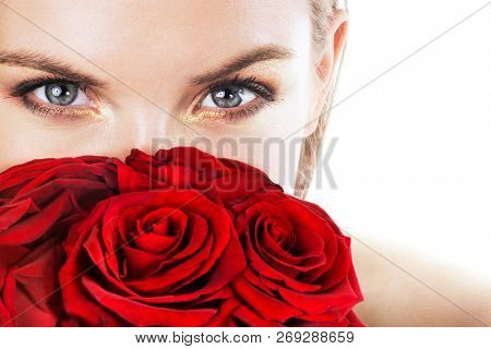 Beautiful young woman with red roses. Focus on eyes. Space for text.