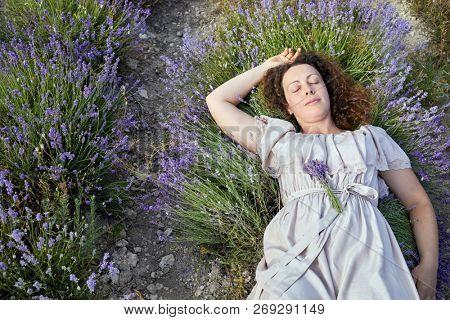 Woman in light dress sleeps om lavender field.