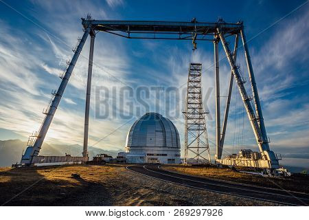 A Special Astrophysical Observatory And A Crane Against The Background Of The Sunset Sky And Snowy P