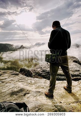 Hiker With Camera In Hands. Photographer Takes Fall Photos With Digital Camera On Peak Above Misty A