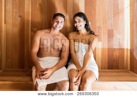 Smiling Man And Woman Wrapped In Towels Enjoying Steam Bath Together At Sauna Bath During Honeymoon