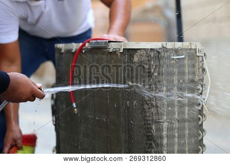 Worker To Cleaning Coil Cooler Of Air Conditioner By Water For Clean A Dust On The Wall In Customer