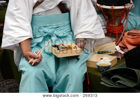 japanese man in traditional clothes eating bento (boxed lunch) prior to the ji-dai matsuri parade in kyoto, japan. poster