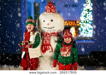 Child Building Snowman. Kids Build Snow Man. Little Boy Playing Outdoors On Snowy Winter Day. Outdoo