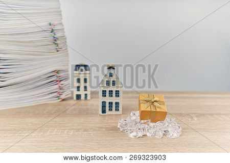 Golden Gift Box On Ice Have Blur House And Stack Of Overload Paperwork Report On Wooden Table With W