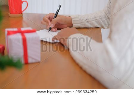 Man Wearing Cream Sweater Writing Christmas Letter Greeting Card Holiday Wishes With Xmas Decoration