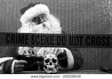 Santa Claus. Santa Crime Scene. Santa Claus holds a Gun and Knife to a Human Skull for an unexpected Evil Santa Photo Shoot. Crime Scene do not cross. Black and White.