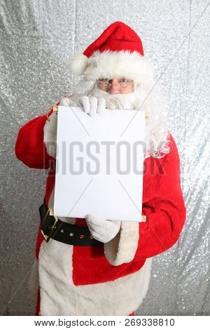 Santa Claus. Santa Claus with his Naughty or Nice List of Good or Bad Children. Good boys and girls. Bad boys and Girls. Blank List. Room for text. Merry Christmas list. Gift list. Your Name Here