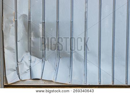 Close-up Of Dented Gray Garage Metal Door
