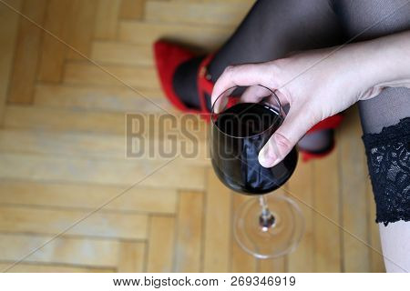 Girl In Sexy Lingerie Sits With A Glass Of Red Wine In Her Hand. Concept Of A Failed Date, Lonelines