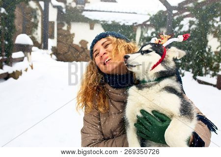 Attractive Caucasian Woman Hugs Funny Malamute Dog Wearing Santa Dear Christmas Antlers. Curly Smili