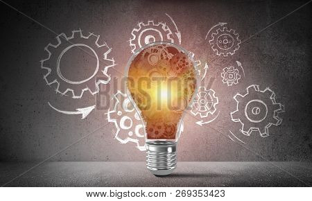 Shining Lightbulb With Multiple Gears Inside Placed Against Sketched Gear Mechanism On Grey Wall On