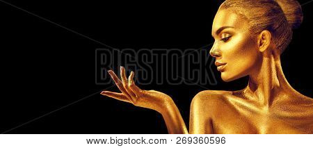Gold Christmas Woman. Beauty fashion model girl with Golden make up, hair and jewellery, pointing hand on black background. Gold glowing skin. Metallic, glance Fashion art portrait, Hairstyle, make up poster