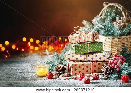 Merry Christmas And Happy New Year. Basket With Christmas Toys And Christmas Gifts On A Wooden Backg