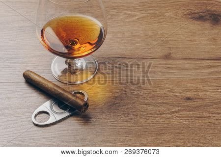 Close Up Of A Cuban Cigar On A Stainless Steel Cigar Cutter And A Snifter Glass Of Brandy On The Woo