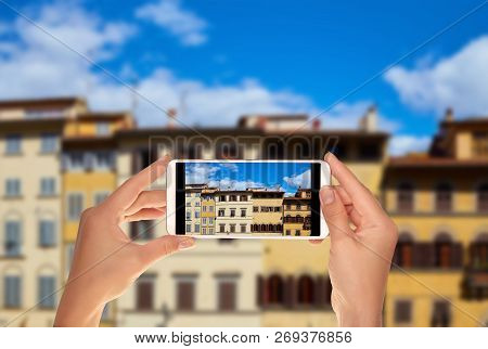 A Tourist Is Taking A Photo Of Facades Of Different Old Houses On Piazza De Pitti In Florence, Italy