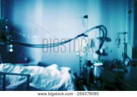 Psychiatric Dismal Cell (ward) With Equipment And A Bed. Blurred Dark Blue Medical Background.