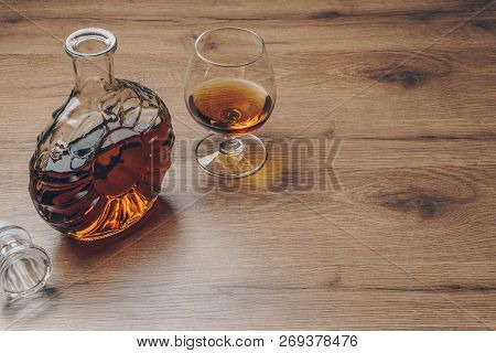 A Snifter Glass Of Brandy And A Brandy Decanter On The Wooden Table