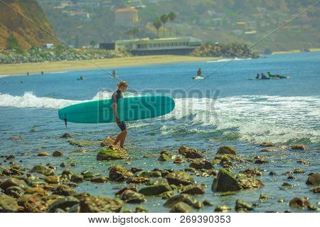 Malibu, California, United States - August 7, 2018: Surfer Holds Surfboard And Walks To The Sea On T