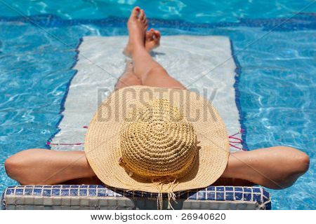 Woman in hat relaxing on holiday on swimming pool bed