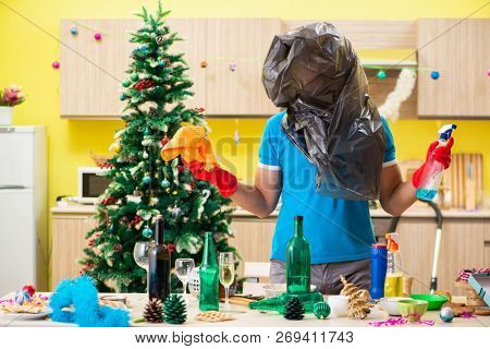 Young man cleaning kitchen after Christmas party