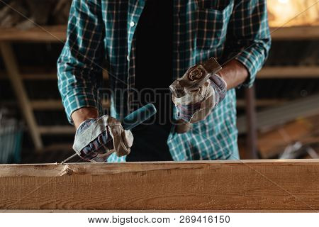 Carpenter With A Hammer And Chisel Handles Wood. Joiner At Work In The Workshop. Home Workshop, With