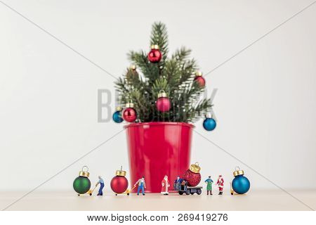 Miniature People Decorating Giant Christmas Tree In Red Pot.