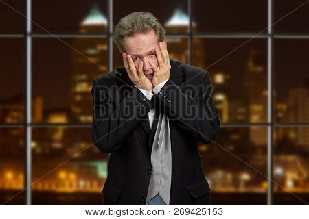 Depressed Businessman Holding Hands On Face. Middle-aged Man In Business Suit In Full Despair On Eve