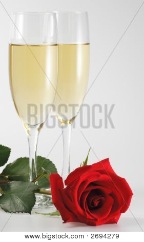 Two Goblets Of Champagne And Red Rose