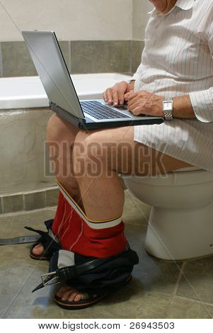 Man working with his laptop in WC