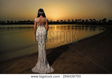 Woman In White Dress In Sunset Beach. Bride And Wedding Ceremony. Elegance And Fashion Model. Weddin