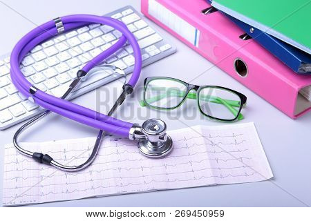 Medical Record Concept With Stethoscope Over Pile Of Folders. Keyboard, Glasses, Pen, Rx Prescriptio