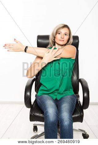 Young Businesswoman Sitting On Chair Doing Fitness Exercise At Workplace