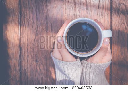 Woman Hand In Warm Sweater Holding A Cup Of Coffee On A Wooden Table Background, Top View