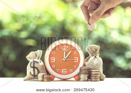Money Savings, Investment, Time And Money Growing Concept : Hand Holding Coin Over Moneybags And Ora