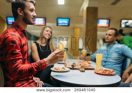 Friends drinks and eats pizza in bowling club