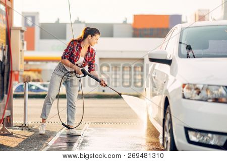 Cute woman cleans car wheels with water gun