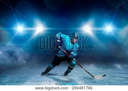 One hockey player on ice, spotlights on background
