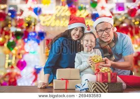 Little Asian Girl And Her Parents With Christmas Gift Boxes Smiling At Camera