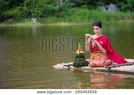 Beautiful Thai Girl Wearing Red Thai Traditional Dress Praying On River Raft In Loy Krathong Festiva