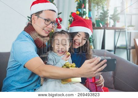Asian Family Opening Their Presents Together And Taking Photo By Smart Phone On Christmas Morning. T