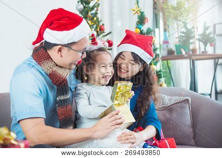 Asian Family Opening Their Presents Together On Christmas Morning. They Are Sitting On Sofa In Their