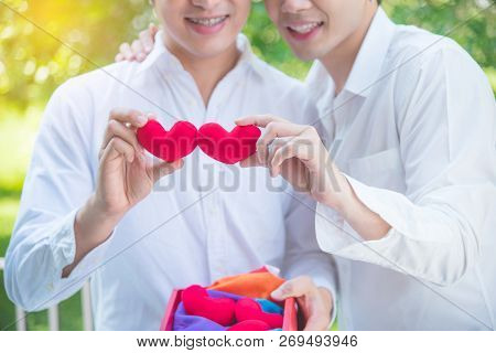 Young Asian Homosexual Couple Holding Red Color Heart Shape And Smile Together