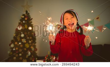 Little Asian Girl Holding Sparkle Firework And Smile In Room With Christmas Decoration At Christmas