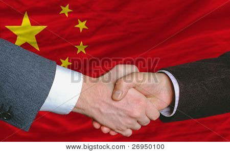 businessmen handshakeafter good deal in front of china flag poster