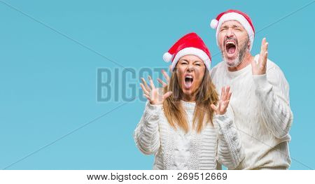 Middle age hispanic couple wearing christmas hat over isolated background crazy and mad shouting and yelling with aggressive expression and arms raised. Frustration concept.